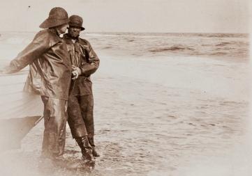 Men in foul wether gear. Fishermen standing in water.. (Nat. Lib. of Norway/USPD/Commons.wikimedia.org)