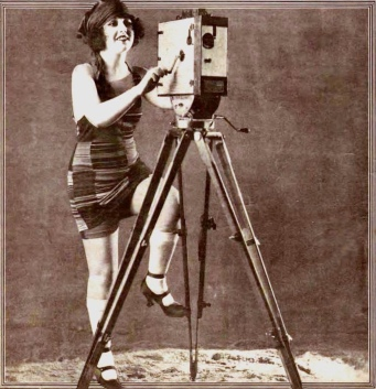 Woman in vintage bathing suit with movie camera. Silent film star Charlotte Rich.Feb.1922 NAtsional Police Gazette. (USPD. pub.date, artist life/Commons.wikimedia.org)