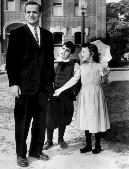 Man in suit and two annoyed children in vintage clothing. Twilight Zone promo photo. CBS/USPD. pub.date, artist life, no cr/Commons.wikimedia.org)