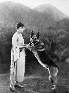 Woman and dog Bothe standing on 2 legs.. Actress and German Shepherd dog star Strongheart. 1923, Photo Play (USPD. pub date, artist life/Commons.wikimedia.org)