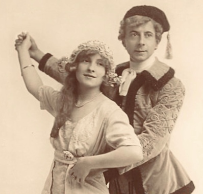 """Woman and man dressed in """"old country"""" ethnic costume. 1913 theatrical postcard. 1913. Guttenberg photo (USPD. pub.date, artist life/Commons.wikimedia.org)"""