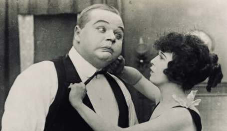 Woman fixing man's tie. couple in vintage 1916 film, The Waiters' Ball. Keystone Film Co./USPD.pub.date, artist life, publicity still/Commons.wikimedia.org)