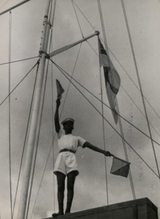 Man on boat.Flag Signals by sailor among boat shrouds. The National Archives UK (PD/Commons.wikimedia.org)