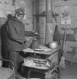 Man cooking over wood stove. (USPD. NARA.HInes. by fed employee/pub.date/Commons.wikmedia.org)