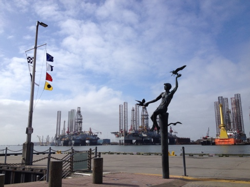Statue of man and seagulls on Pier 21 of Galveston, TX.Three jackup rigs in for service across channel behind him. (Image: all rights reserved./copyrighted/ NO permissions granted)