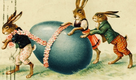 Three Bunnies rolling a very large Easter egg. Old Russian postcard, ca.1917 (USPD.pub.date, artist life/Commons.wikimedia.org)