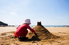 Boy on beach making a sandcastle (released to PD by Fadhela/Commons.wikimedia.org)