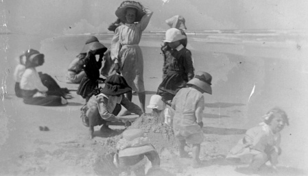 Vintage dressed children playing in sand at beach. 1900-1910. (John Oxley Lib., Queensland released to PD, pub.date/Commons.wikimedia.org)