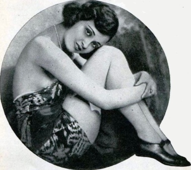 woman in vintage bathing suit sitting curled up holding knees (1921 promo photo. Dolores Mendez Broadway show. for the Tatler May 1921. (USPD. pub.date, artist life/Commons.wikimedia.org)