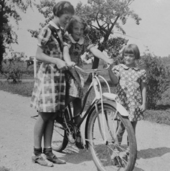 3 girls in fall plaid dresses with bike. 1930's (Shirl/Flickr/Aunt Owwee/Commons.wikimedia.org