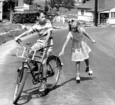 Vintage photo of boy on bike and girl on skates, 1948, (DOE photo(USPD. pub.date, by fed employee, Flickr/Commons.wikimedia:org)