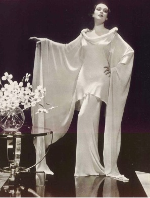 elegant woman standing in long white dress. (USPD/pub.date/publicity pix of Dolores del Rio for Argentinean Magazine/Commons.wikimedia.org)