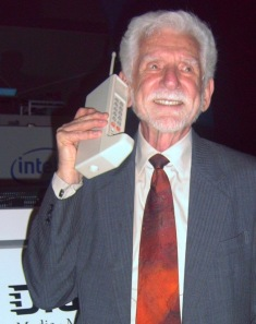 man with vintage cell phone. prototype Dyna TAC Motorola phone held by Martin Cooper (who made the first on) (Image by Rico Shen/Commons.wikimedia.org)