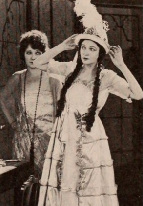 2 women in. vintage dresses. 1920 (USPD pub.date, artist life/Commons.,wikimedia.org)