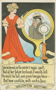Halloween vintage greeting card of woman looking to mirror and contemplating a man's image. T.R.Co. NY Pub.Lib. (USPD. pub.date/Commons.wikimedia.org)