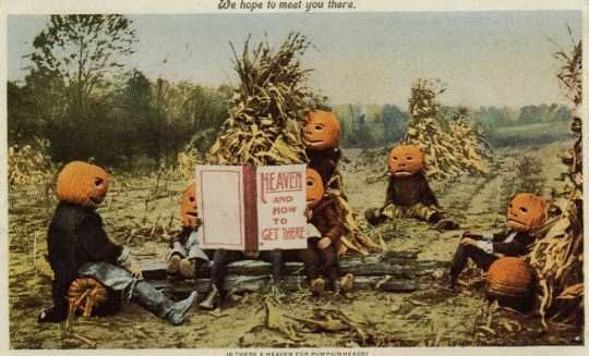 Pumpkinheads sitting in field reading instructions. Halloween card. 1901. USPD.pub.date, artist life/Commons.wikimedia.org)