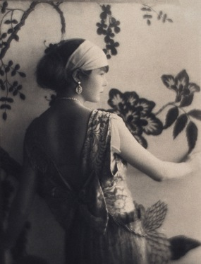 1920 woman by wall paper. (USPD. pub date, LoC/ Commons.wikimedia.org)