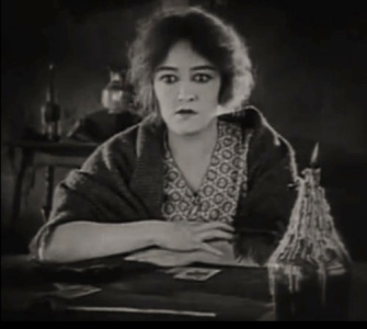 Exhausted woman at table. (Gladys Brockwell, 1922 screenshot from Oliver Twist/First NAt. Pictures (USPD. pub.date, artist life/Commons.wikimedia.org)