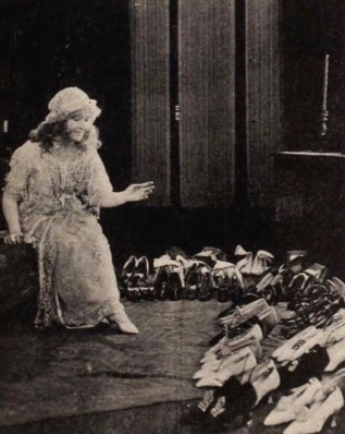 Woman surrounded by rows ands rows of shoes. Bessie Barriscale, 1921, Exhibitors Herald, 1921. USPD, artist life, pub.date/Commons.wikimedia.org)