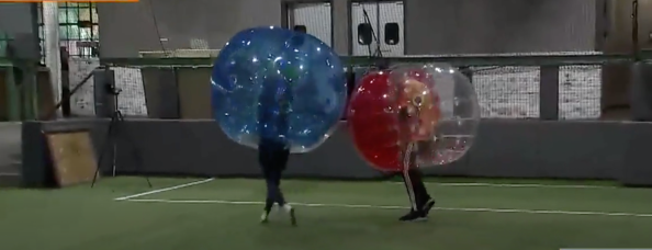 Two bubble soccer players make contact (screenshot ch 26 news Houston)