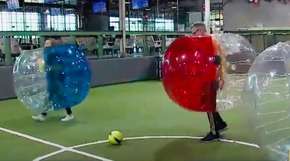 Two people in red and blue bubbles playing soccer (Screenshot ch 26 news Houston)