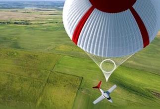 Aircraft with parachute deployed over green field ((AlphaLux webzine)