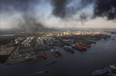 Vessels and tank farm under ITC fire smoke plume on Monday (Marie D. De Jesus, Houston Chronicle photographer)