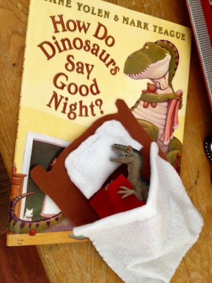 Dinosaur in bed with red blanket with Dino book in back (© image: all rights reserved, copyrighted, no permissions granted)