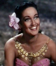 Woman with tropical flower. Dorothy Lamour in Road to Bali, 1951 (USPD pub.date, artist life/Commons.wikimedia.org)