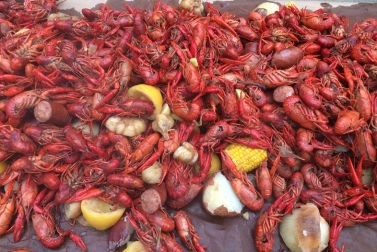 """Boiled crawfish spread out on table ready to eat. You see ethnic food delicacy, I see scenes from the 1970 film """"Night of the Living Dead""""...humans greedily gnawing with their moist fingers and sucking out brains... (Ykamo/Commons.wikimedia.org)"""