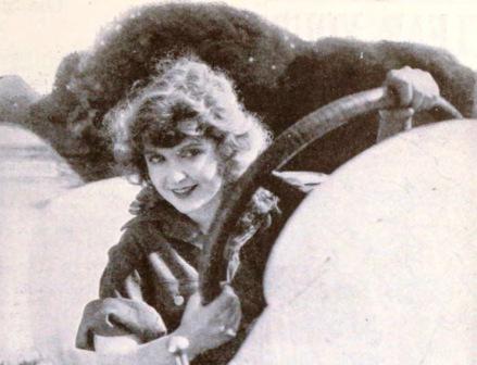 Woman steering vintage car. May Allison, 1921 Phototplay mag./USPD.pub.date, artist life/Commons.wikimedia.org)