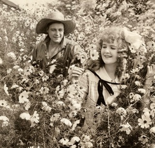 Man and woman in flowers. ( 1916 movie Big Tremaine. May Allison/USPD. pub.date, artist life/Commons.wikimedia.org