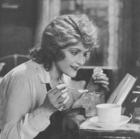 Vintage woman reading and eating at table (1919 Lobby card for Castles in the Air film/May Allison/USPD.pub.date, artist life/Commons.wikimedia.org)