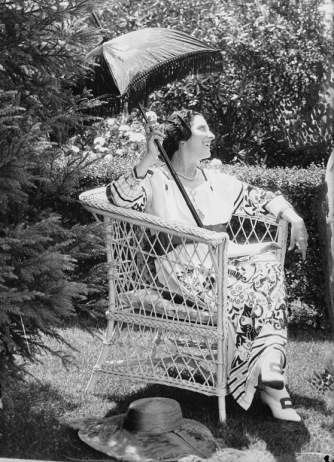 Woman sitting in garden with parasol (1899.Bain News Service/LoC/USPD. pub.date, artist life/Commons.wikimedia.org)