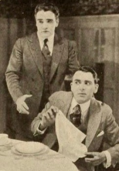 Two worried men at table. 1918 Motion Picure News/Triangle Films Corp. /USPD. pub.date, artist life/Commons.wikimedia.org)