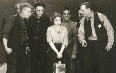 woman surrounded by men. 1917 film Triangle Film Corp.(USPD.pub.date, artist life/Commons.wikimedia.org)