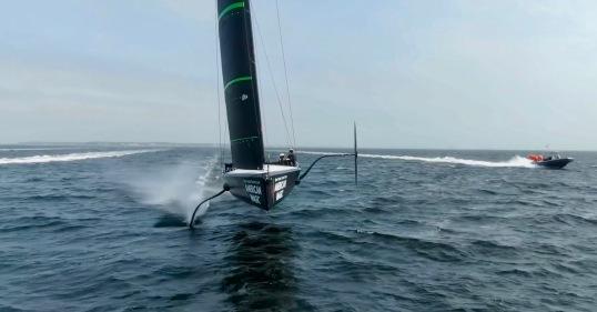 Race between sailboat on fails and motor boat (Screenshot, The Sailing Show)