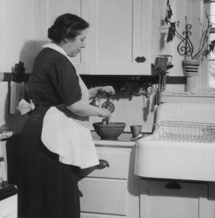 Woman cooking in kitchen. 1920-1954 (NARA/USPD.pub.date, artist life/Comons.wikimedia.org)