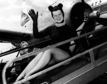 Woman dressed as cat sitting on vintage plane (Kitirik mascot 1958. (KTRK publicity photo/Hou.Chron)