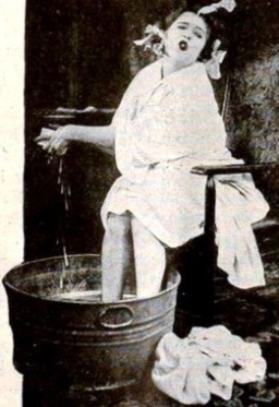 Woman taking bath in wash tub of water. Mae Murry. Universal Films, 1919. (USPD. pub.date, artist life/Commons.wikimedia.org)