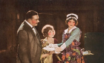 Servants, two women and a man, with a tray. (1921 Lobby movie card from RealArt Flims/USPD. pub.date, artist life/.Commons.wikimedia.org)