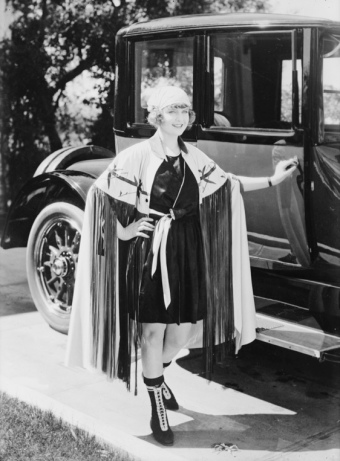 Woman standing by vintage car . 1899 (Bain News Service/LoC/USPD. pub.date, artist life/Commons.wikimedia.org)