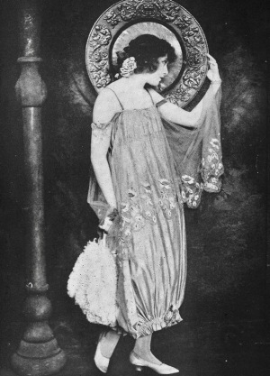 Standing woman in vintage dress with large platter and feather fan. 1920. Shadowland mag., Witzel (USPD. artist life, pub. date/Commons.wikimedia.org)