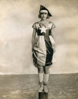 Woman in patriotic costume standing on pier. 1917. Sayre collection of Theatrical Photo. (USPD. pub.date, artist life/Common.wikimedia.org)