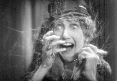 Scared woman in spider webs. Carrie Daumery in movie The Last Warning(USPD, pub.date of 1927, artist life/Commons.wikimedia.org)