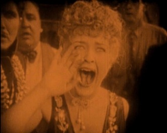Yelling woman among other people. (Laura La Plante in film, The LAst Warning (1928) (USPD. pub.date, artist life/Commons.wikimedia.org)