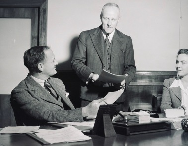 Two men and a woman at a desk. Librarians in New South Wales, 1943. (USPD. pub.date, released/OTRS/Commons.wikimedia.org