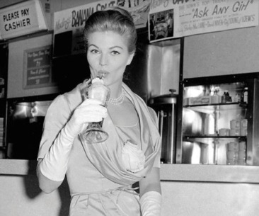 Woman sipping a milkshake at 1950's drug store Counter (Image from Houstonia)