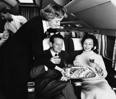 1950's AIrhostess serving passengers snacks (SAS Scandinvian Airlines. USPD: pub.date, artist life/Commons.wikimedia.org)