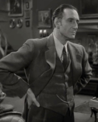 """Man in vintage suit standing with hands on hips. Actor Basil Rathbone in 1946 """"Dressed to Kill"""". Universal Pictures (USPD.pub.date, artist life/Commons.wikimedia.org)"""
